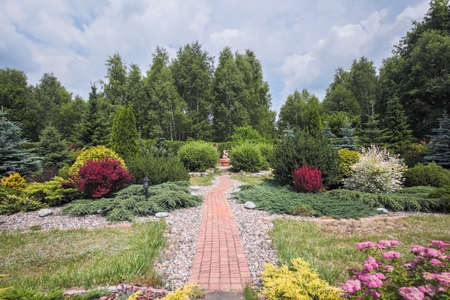 cobbled: Photo of beautiful garden with blooming bushes and cobbled path Stock Photo