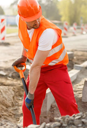 brick road: Male construction worker is digging a hole