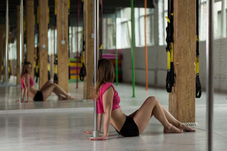 dance studio: Girl in pole dance studio sitting by the mirror