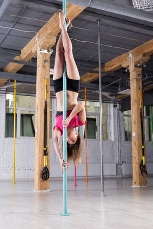 practicing: Upside down sporty woman performing pole dance