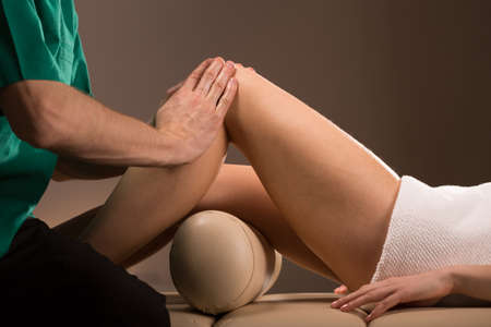 stroking: Close-up of massage therapist stroking female legs