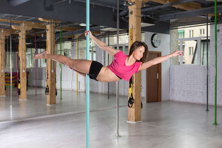 Young talented pole dancer practicing in fitness club Stock Photo