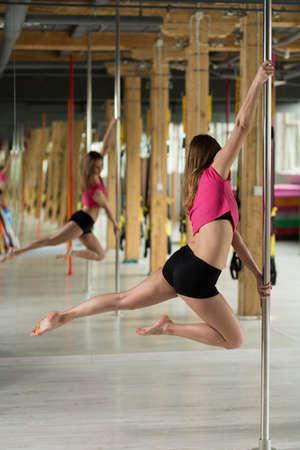 impressive: Female pole dancer in acrobatic pose reflecting in mirror