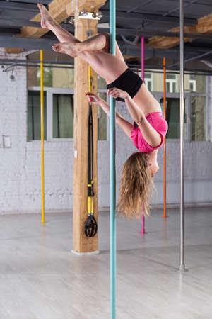 cabeza abajo: La chica joven boca abajo en el poste en el estudio de danza