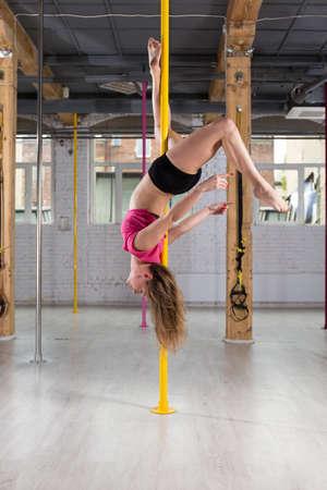 cabeza abajo: Atl�tico bailarina de barra invertida en el poste
