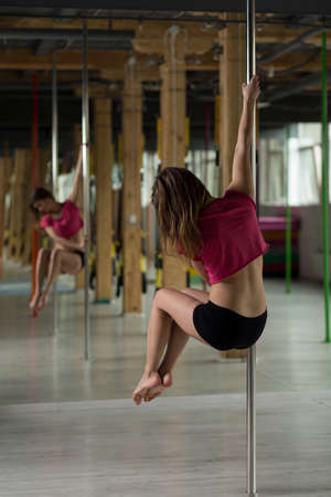 sexy dancer: Woman dancing on the pole in dance studio Stock Photo