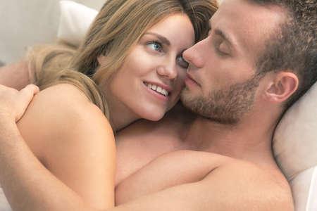pareja desnuda: Primer plano de la pareja desnuda abrazando en la cama