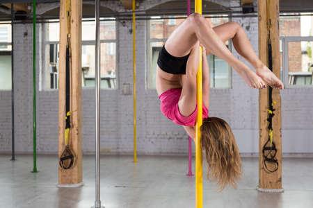 taniec: Elastyczne młoda kobieta robi taniec na rurze w klubie fitness Zdjęcie Seryjne