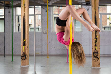 pole dance: Flessibile giovane donna facendo pole dance fitness club