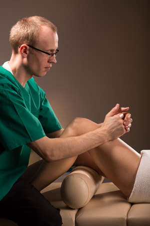 manuals: Middle aged masseur therapist working with patient