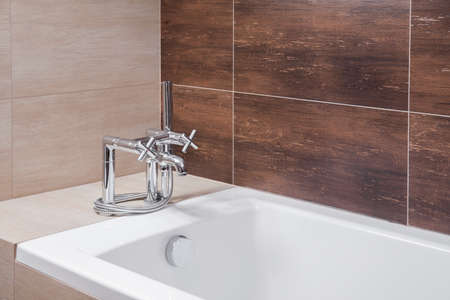 areas: Close up of white bathtub with old style silver tap