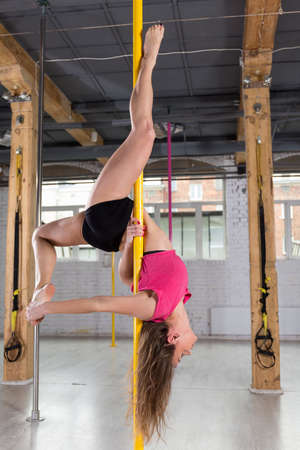 impressive: Young fit girl performing impressive pole dance