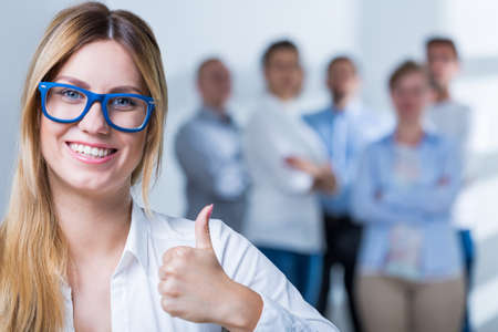 specs: Smiling businesswoman with spectacles showing thumb up Stock Photo