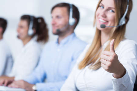 representatives: Attractive call center operator showing thumb up Stock Photo