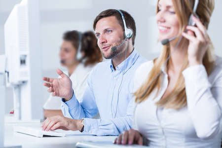 Jeune équipe du centre d'appel de parler avec les clients