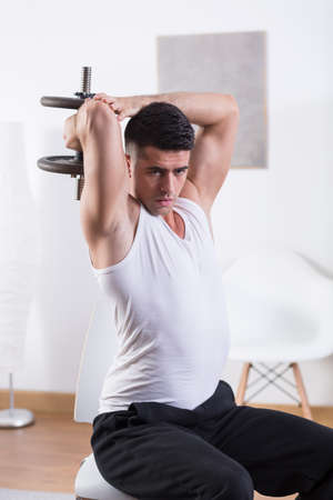 strengthening: Sporty man with dumbbell strengthening triceps muscle Stock Photo