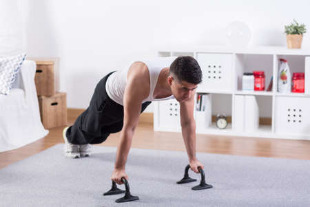 exercise room: Attractive bodybuilder doing push ups in room