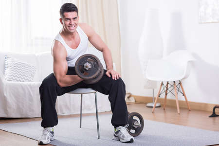 flexion: Muscular man training with dumbbell at home