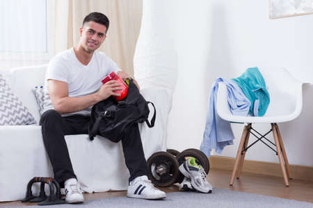 sportsmen: Sporty man packing protein powder to the bag