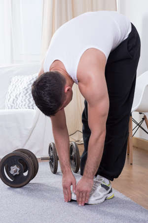 hamstring: Young muscular man stretching legs at home