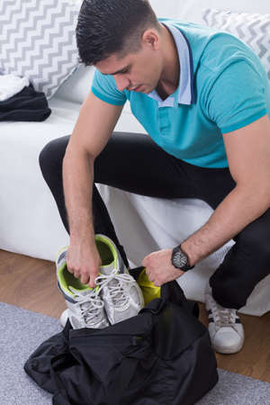 Young man packing gym bag before training