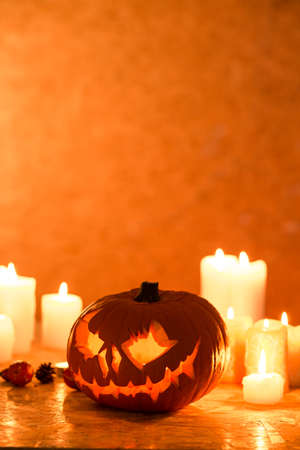 halloween background: Halloween pumpkin lantern and candles on the table