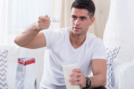 of shake: Handsome bodybuilder preparing protein shake before workout Stock Photo