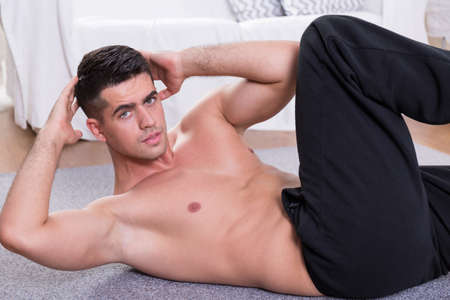 oblique: Sporty man doing oblique crunches on the floor