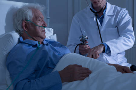 asleep: View of asleep old patient being examined by doctor Stock Photo