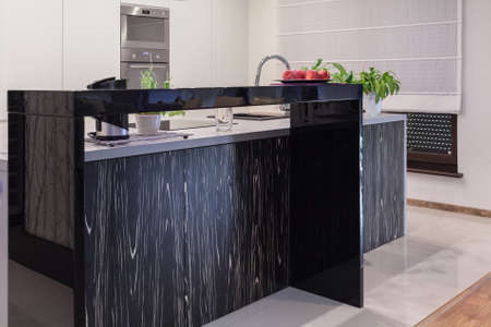 kitchen island: Image of luxurious black kitchen island in light interior