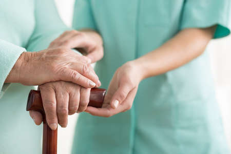 care at home: Close-up of woman using cane assisted by physiotherapist Stock Photo