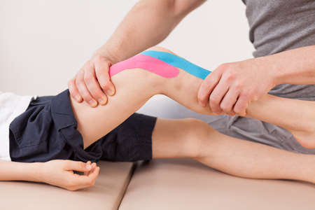 therapy room: Close up of small boy with kinesio tape doing exercises Stock Photo