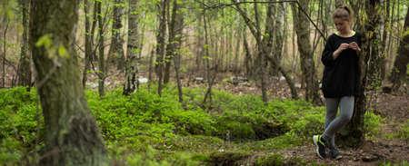 outdoor fitness: Panorama of female runner having break in the forest Stock Photo