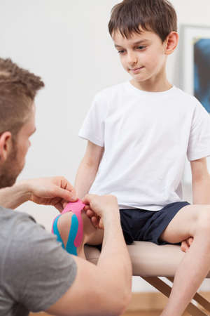 therapy room: Image of small happy boy during kinesiology therapy Stock Photo