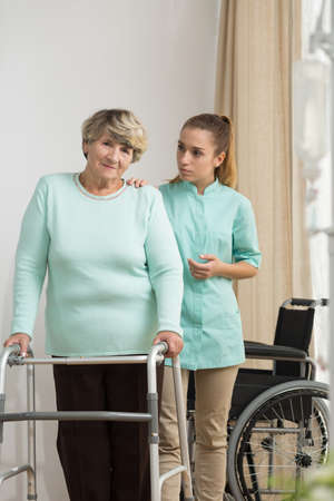 physical impairment: Disabled senior woman standing with walking frame
