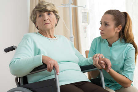 disabled seniors: Disabled sad woman living in care home Stock Photo