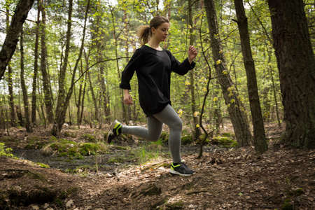 regularly: Image of athletic woman exercising regularly in the park