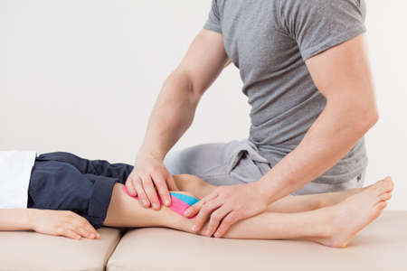 Close up of physical therapist doing massage on child leg