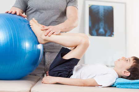 therapy room: Picture of small patient doing exercises with fitness ball