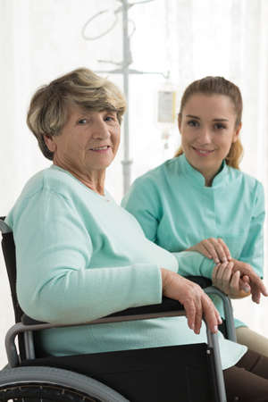 social work aged care: Smiling disabled woman and nurse in care home Stock Photo