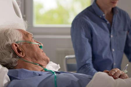 Uitzicht op oudere zieke man wordt bezocht door zijn realtive