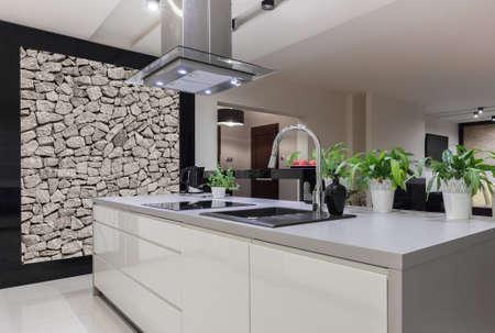 Photo of beautiful white kitchen island with decorative wall Stockfoto