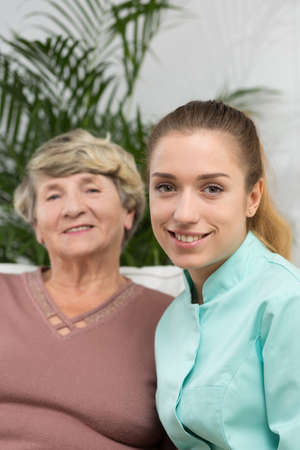 residential home: Elder lady and nurse in residential home Stock Photo