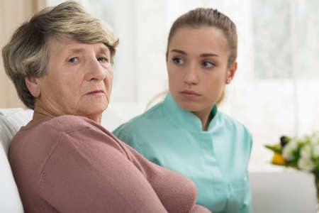 nursing assistant: Depressed senior woman staying in rest home Stock Photo