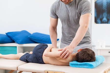 fisioterapia: Fotograf�a de un ni�o acostado en mesa de tratamiento en la sala de rehabilitaci�n