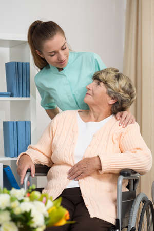 patient care: Disabled woman talking with nurse in rest home