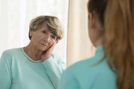 mujer triste: Mujer mayor deprimida hablar con el psicólogo femenina Foto de archivo