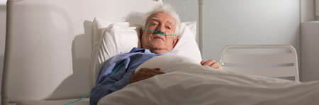 Panoramic view of an elder man in hospital bed Stock Photo