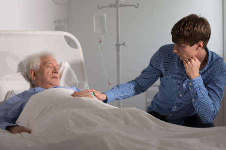 man in hospital bed: Elder ill man sleeping and a relative holding his hand Stock Photo