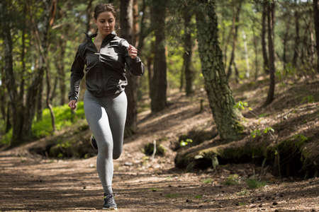 Image of young sportive woman training in the forest Stock Photo
